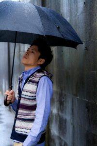 雨の日に傘を差す青年