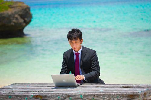 リゾート地でスーツ姿で仕事をするビジネスマン